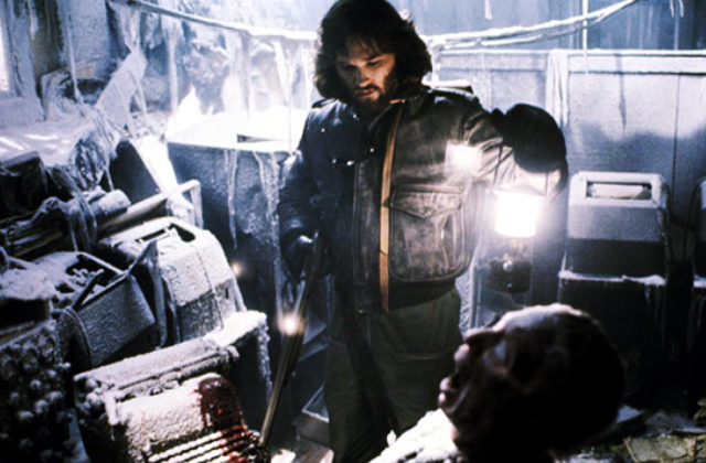 "Image from the film ""The Thing,"" in a frozen room, a man holds a lamntern and looks at a disembodied head."
