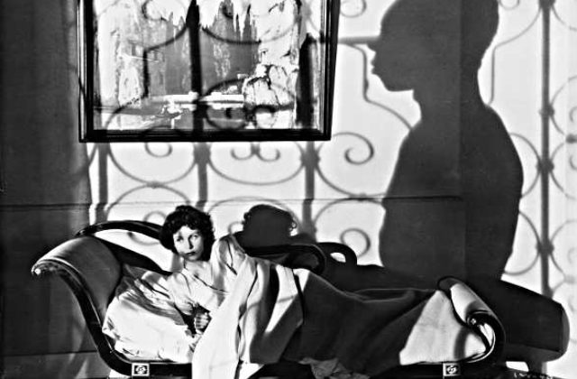 A black and white photo of a white woman lying on a divan, with the shadow of a black man on the wall behind her.
