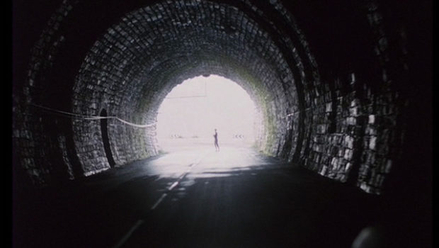 "Image from the film ""Spoorlos"" of a long tunnel, at the end of which, a woman is silhouhetted in the light.e"