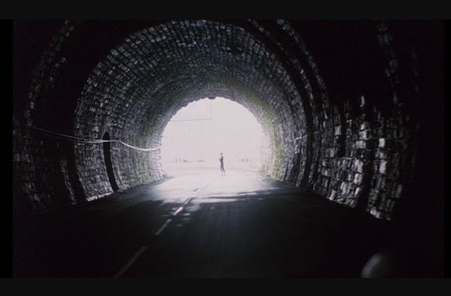 """Image from the film """"Spoorlos"""" of a long tunnel, at the end of which, a woman is silhouhetted in the light.e"""