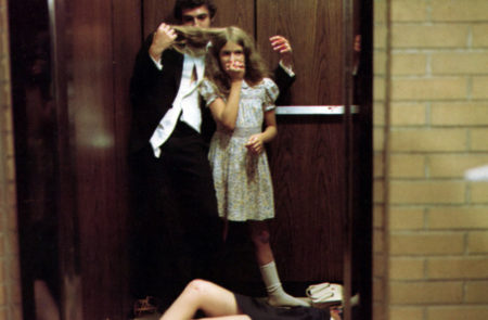 "Image from the film ""Shivers"": A man and a girl are in the an elevator. The man is smelling the girl's hair. There is a body half-seen on the floor."