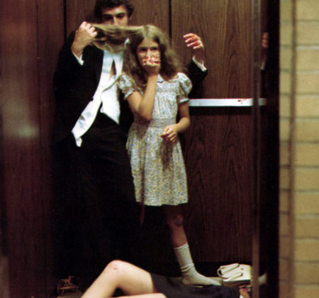 """Image from the film """"Shivers"""": A man and a girl are in the an elevator. The man is smelling the girl's hair. There is a body half-seen on the floor."""